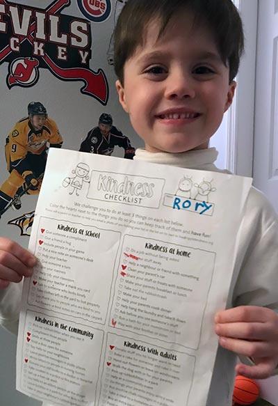 Boy holding a Ripple Kindness Checklist