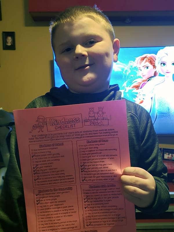 Boy holding her kindness checklist